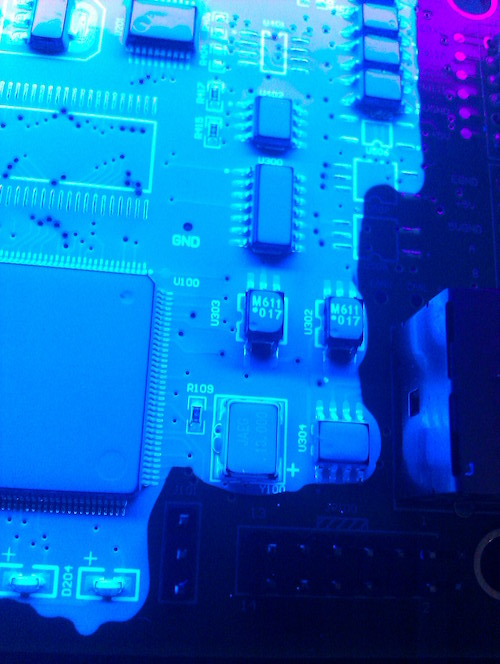 Conformal coating material applied to a circuit board using a selective robot