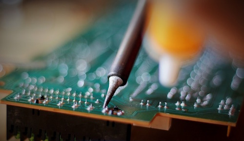 It is possible to solder directly through Parylene coating to remove it